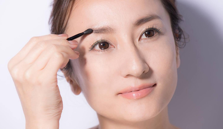 眉を描いている女性