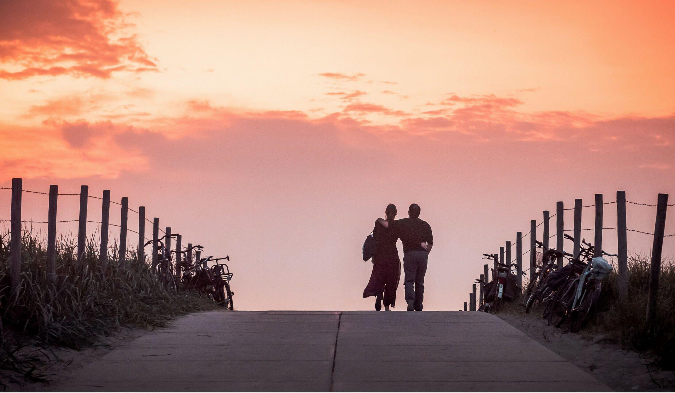 夕焼けの中、真っ直ぐ続く道を男女2人が肩を抱き合って歩いている