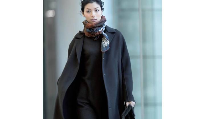 黒コートを着てスカーフを首元に巻いた女性