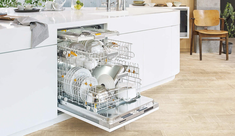 白いシステムキッチンに設置されているビルトイン食洗機が開かれている