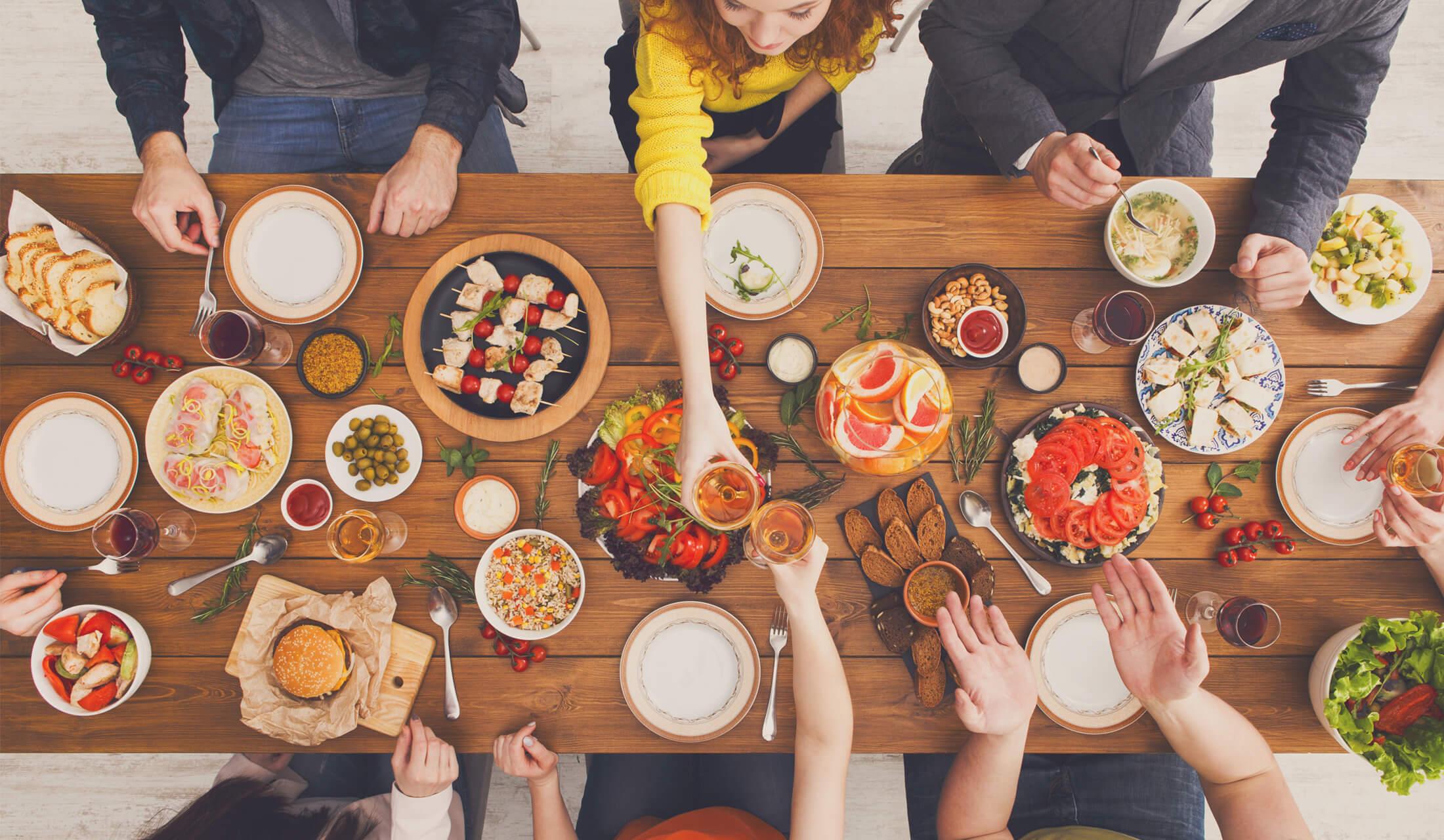料理やドリンクが並んだ長テーブルを6人の男女が囲み、中央の女性2人が机を挟んで乾杯している