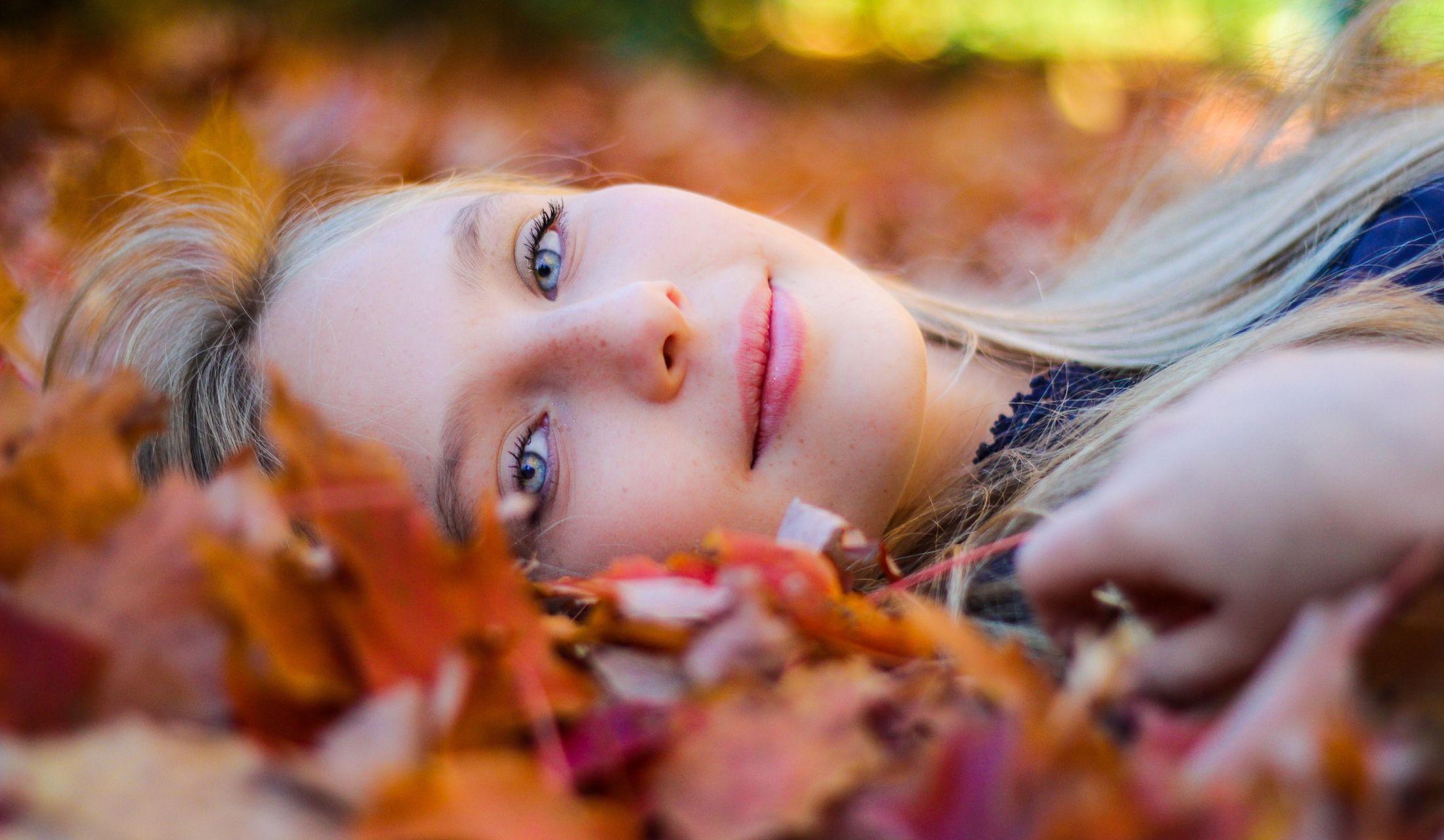 落ち葉の中に横たわる美しい女性