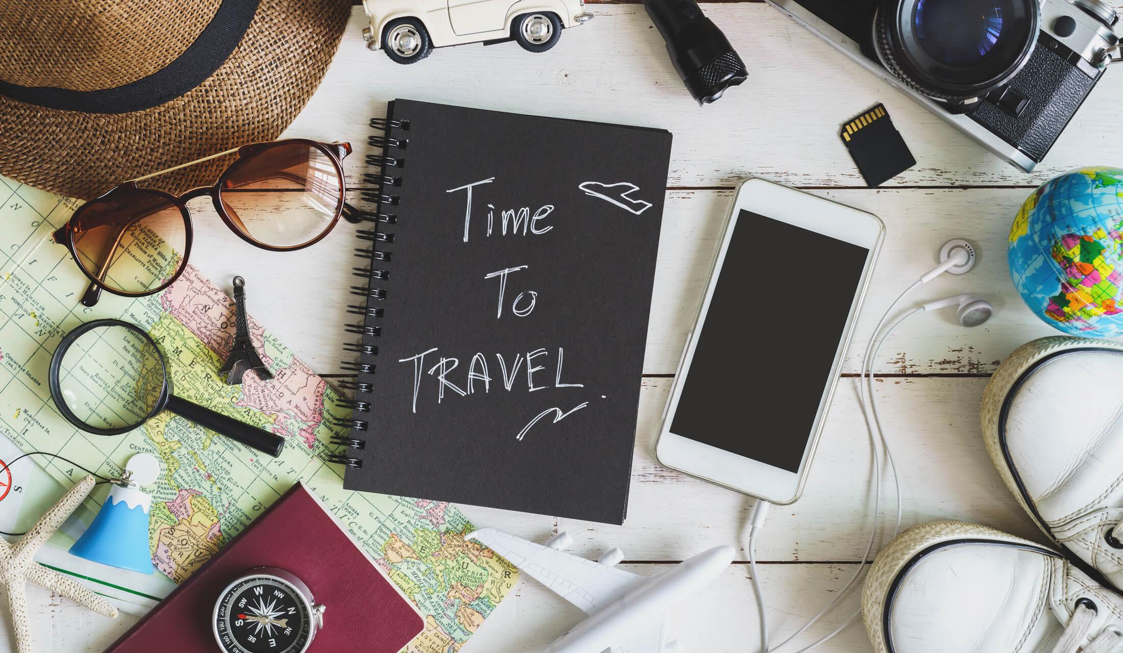 旅行に持っていくノートやサングラス、地図、スニーカー、スマートフォンなどのアイテムが床の上に広げられている様子