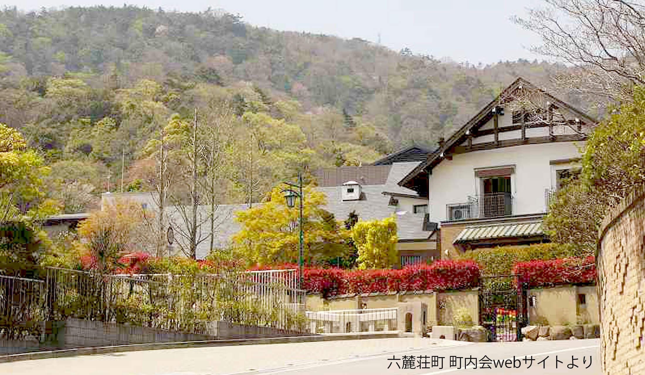 六甲山麓を背景に広い敷地に建つ豪邸。庭には木々が植わっている。