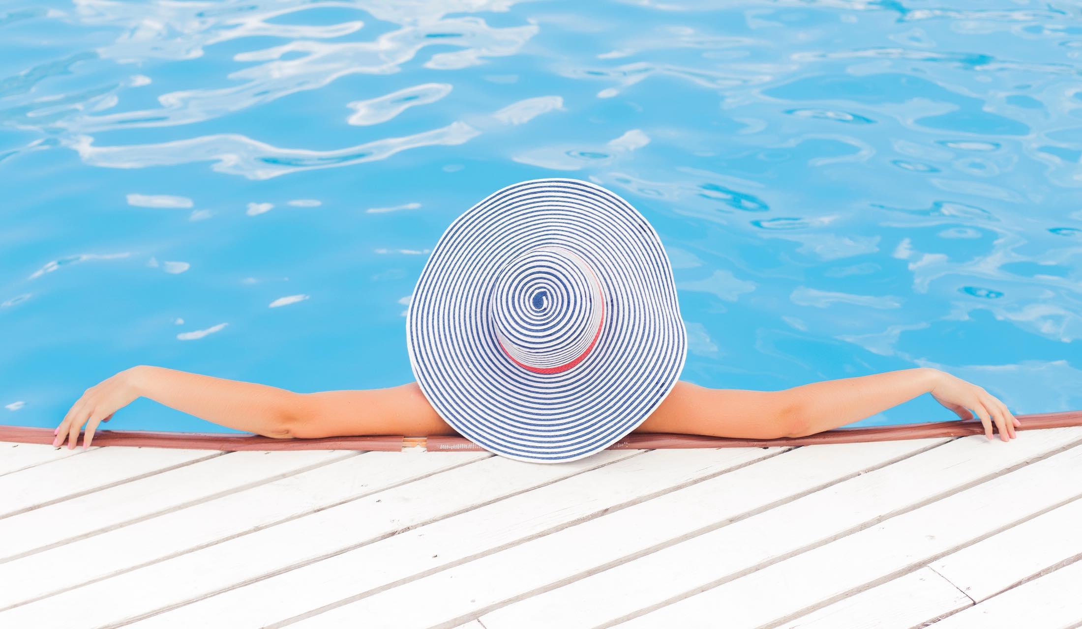プールサイドで両手を広げて帽子をかぶっている女性