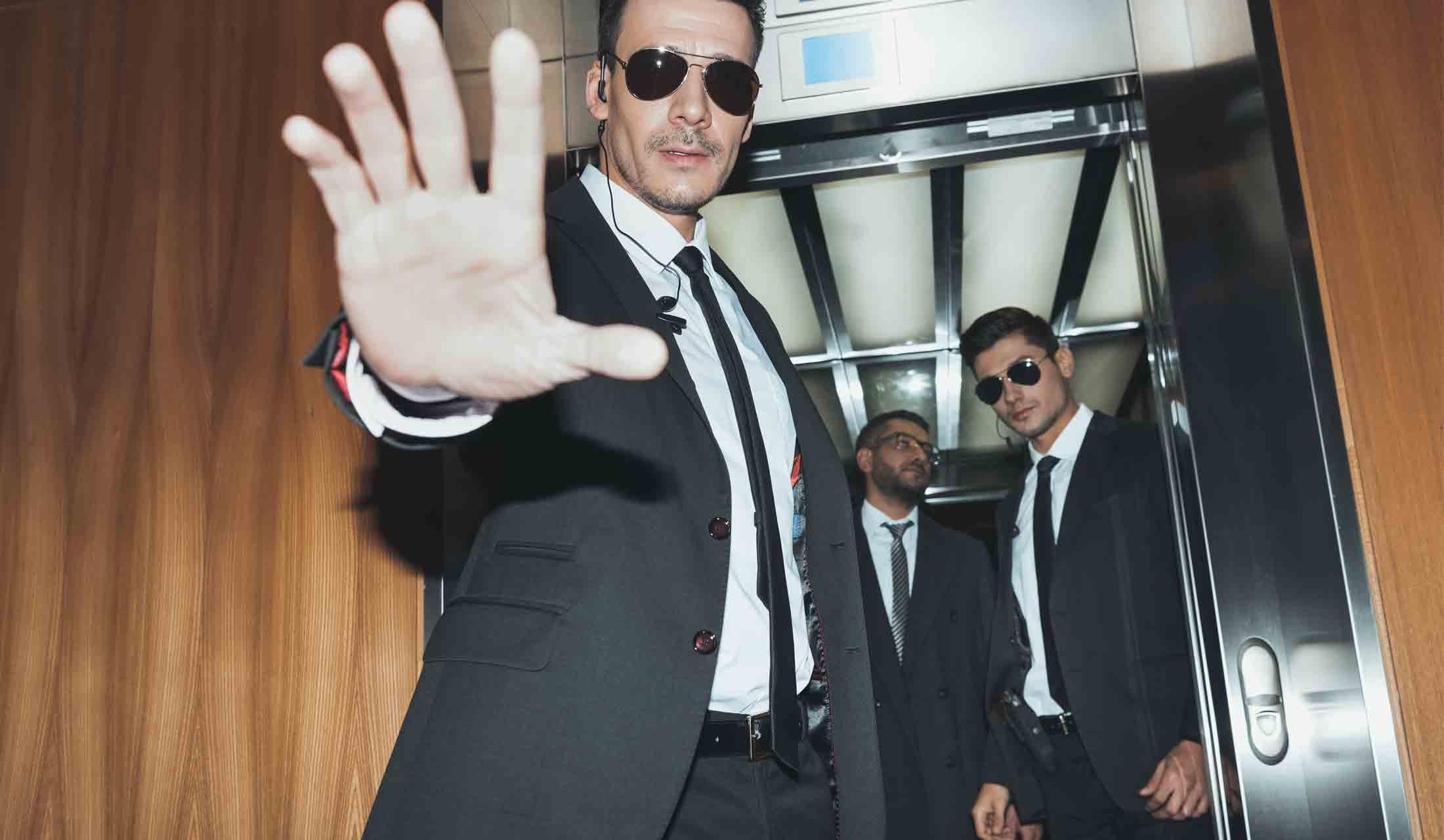 黒いスーツを着た2人のボディーガードがエレベーターに乗る要人を警護している