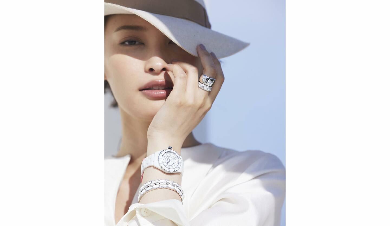 時計『J12』[SS×ホワイトセラミック×ダイヤモンド、直径33mm、クオーツ]¥645,000・ブレスレット各¥1,480,000・リング/指先から¥364,000・¥1,216,000(シャネル)、帽子¥66,000(ボルサリーノ ジャパン)、トップス¥130,000(ミカコ ナカムラ 南青山サロン<MIKAKO NAKAMURA>)