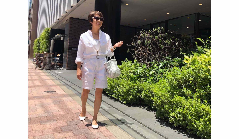 白のオールインワンを着てサングラスをかけた女性が歩いている