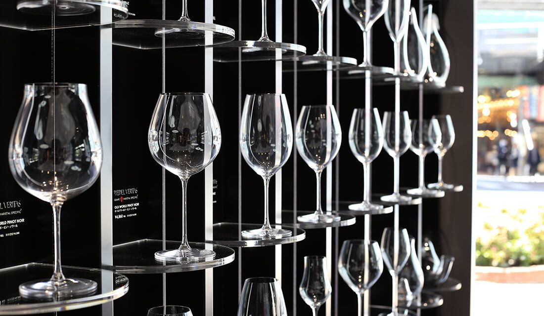 :壁に美しくディスプレイされたリーデルのグラスごとに、マッチングさせたブドウの品種名が書かれています。汎用性が高いものが一目でわかるのもポイント