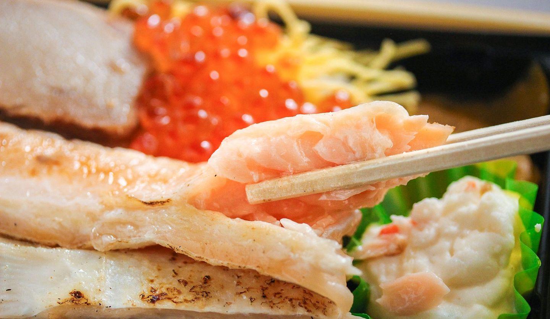 鮭やイクラが敷き詰められたお弁当から、鮭の切れ端を箸で持ち上げている