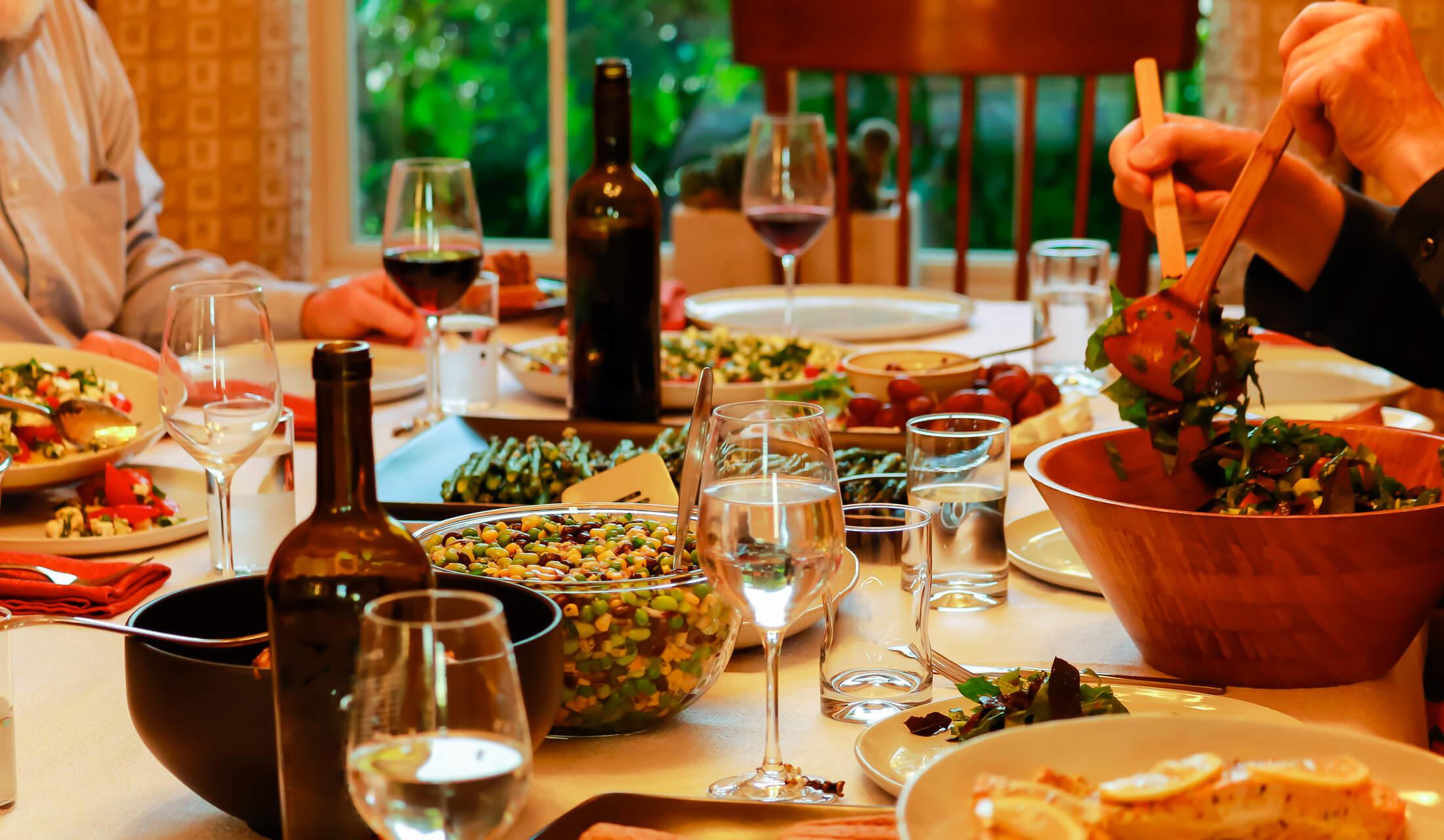 赤ワインやサラダなどがテーブルに上に乗せられ、1名がサラダをお皿へ盛り分けている様子
