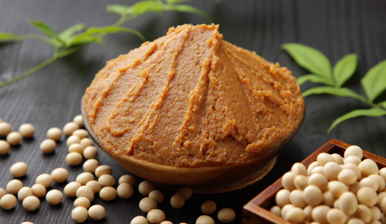 黒い器に茶色い味噌が山盛りにのせられ、その器の周囲に大豆が入れられた升や大豆が直に散らばっている