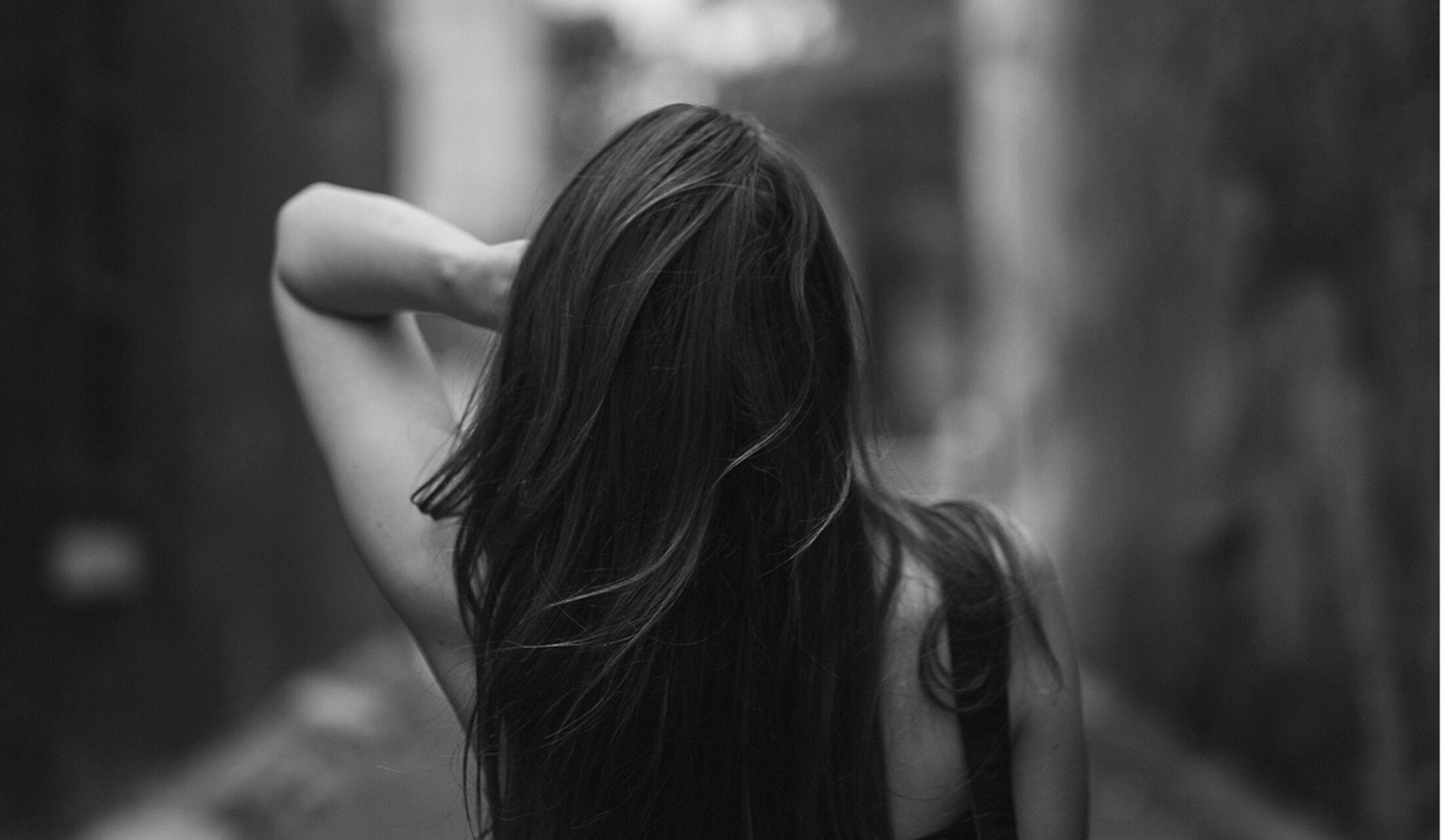 長い髪をなびかせる女性