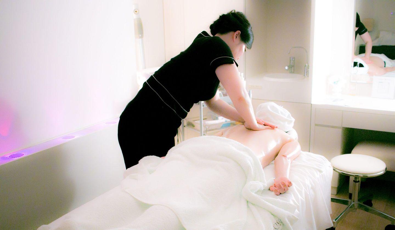 エステティックサロンにて、女性がうつ伏せになり、エスティシャンに背中のマッサージを受けている