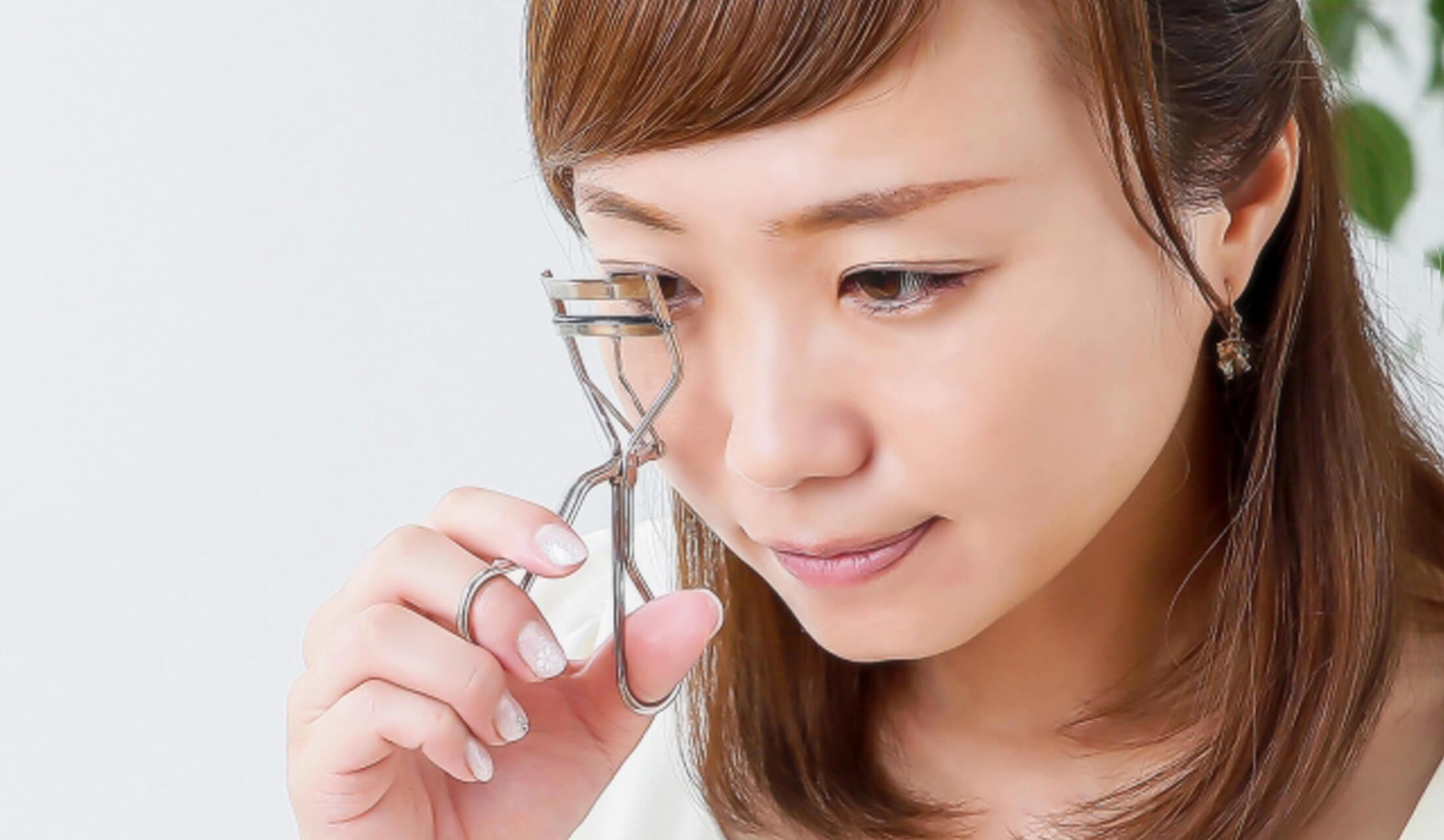 女性がアイラッシュカーラー を使って右目のまつ毛にカールをつけている