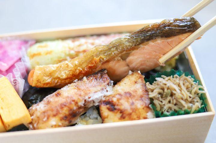 ちりめんじゃこ、鱈の西京揚げ、ちくわの磯部揚げなどが詰まった弁当、鮭を箸でつまんでいる