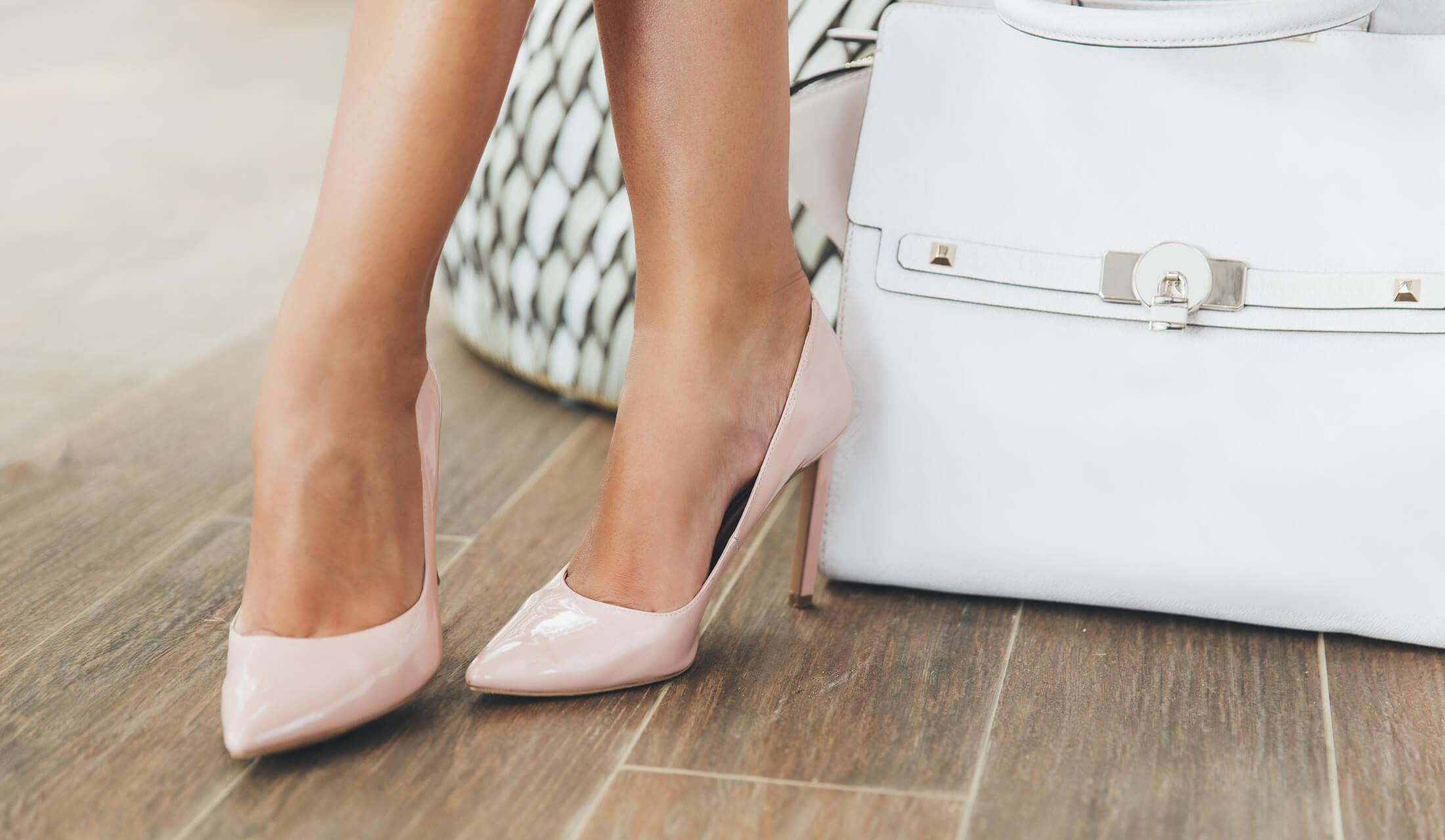 女性が白いカバンの横にベージュピンクのハイヒールを履いて足をクロスしている