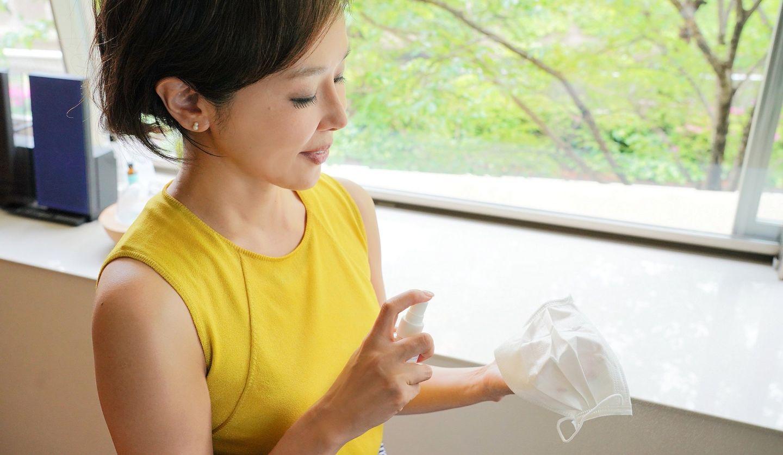 金子エミさんがマスクにスプレーしている