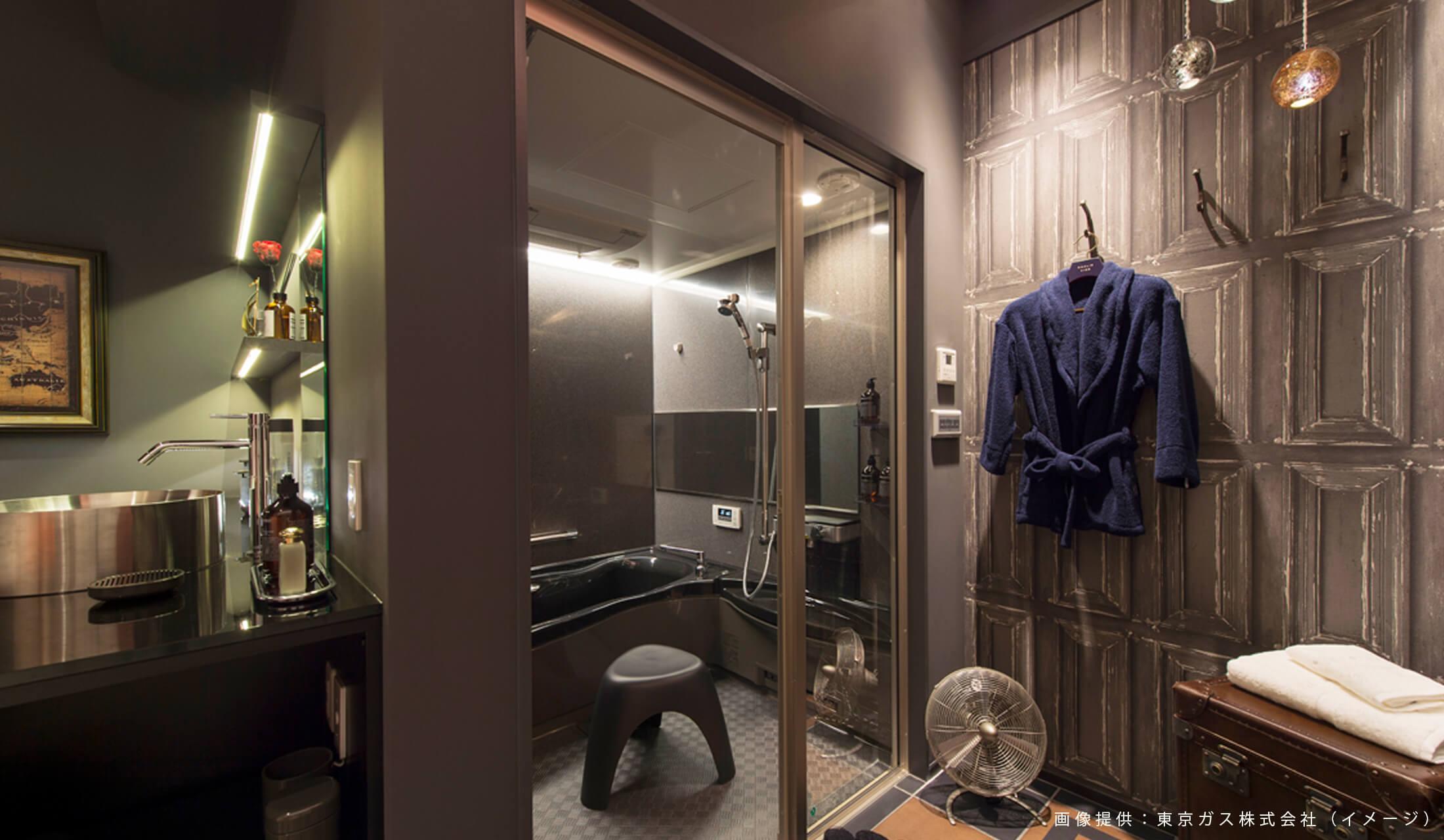 浴室前の壁にはバスローブが掛けられ、黒を基調としたバスルーム内の天井にはミストサウナが設置されている
