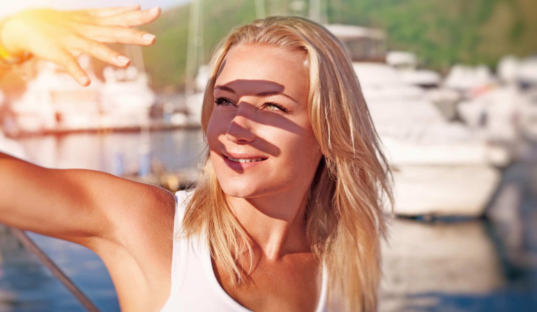 手で顔の日差しを防ぐ女性