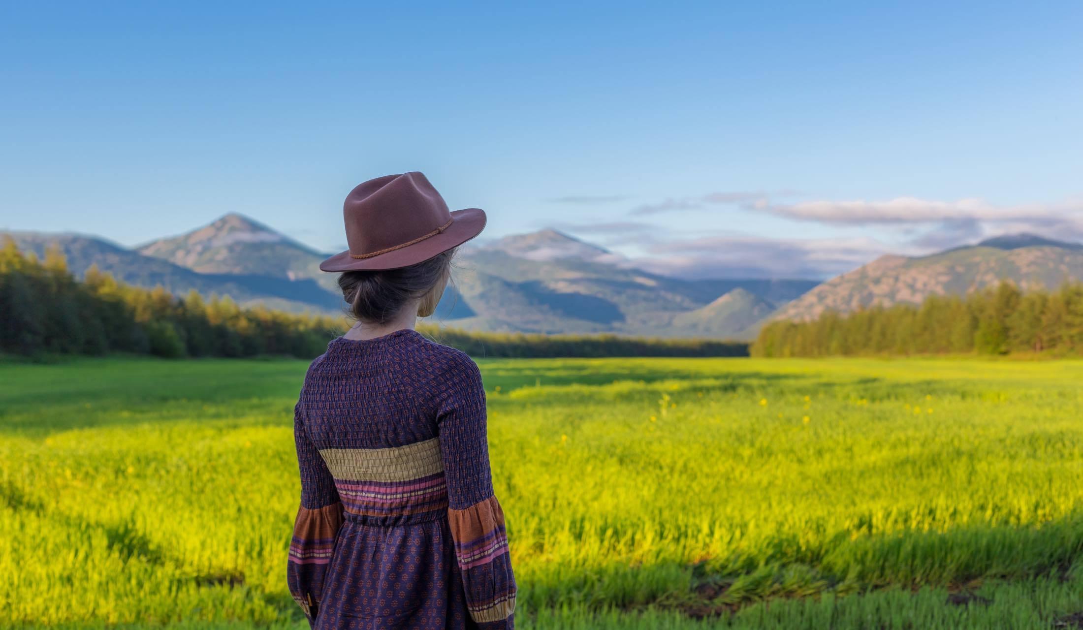 田園を前に帽子をかぶって佇む女性