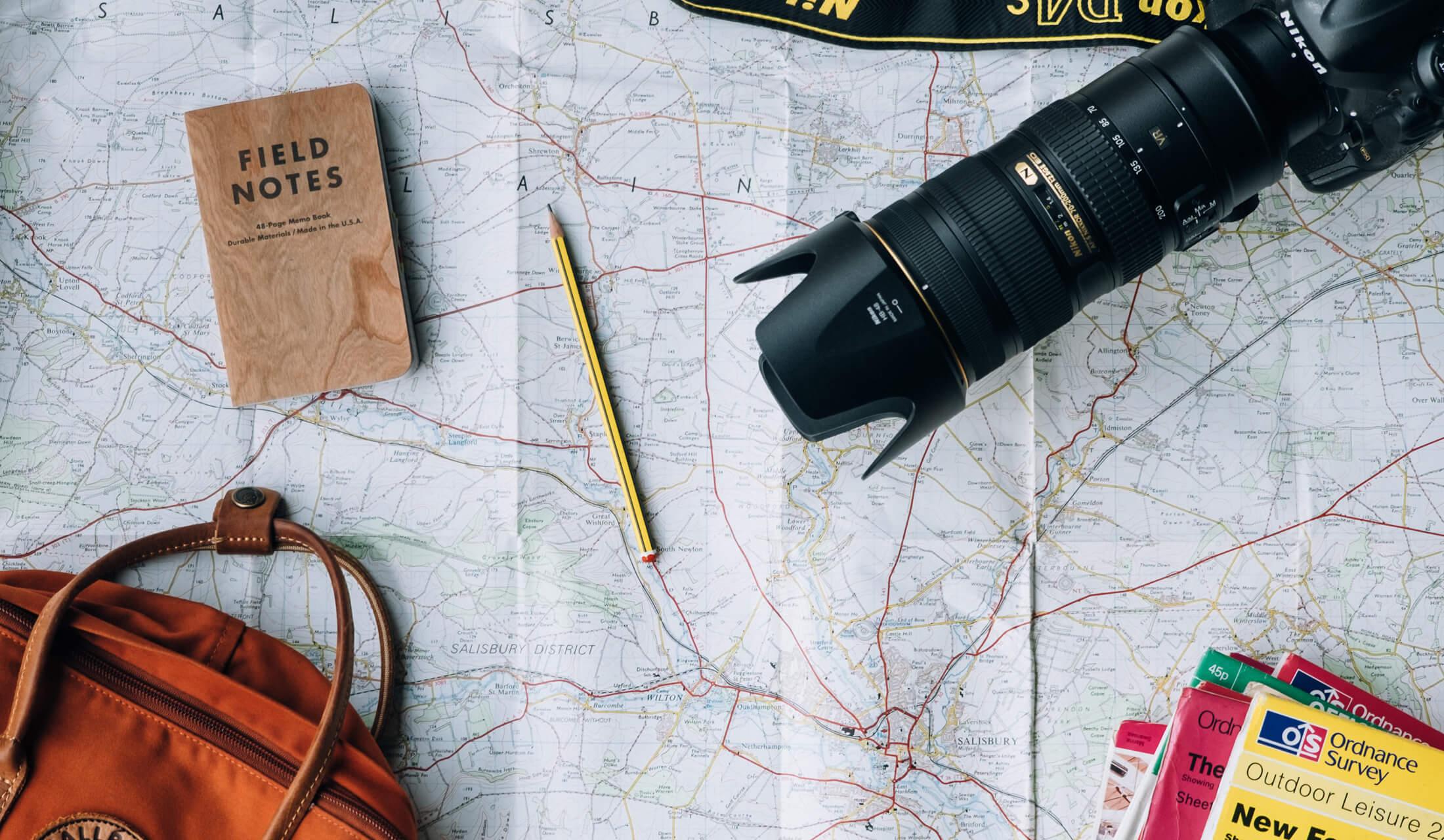 旅行地図を広げてカメラやバッグなどの携行品をチェックしている様子