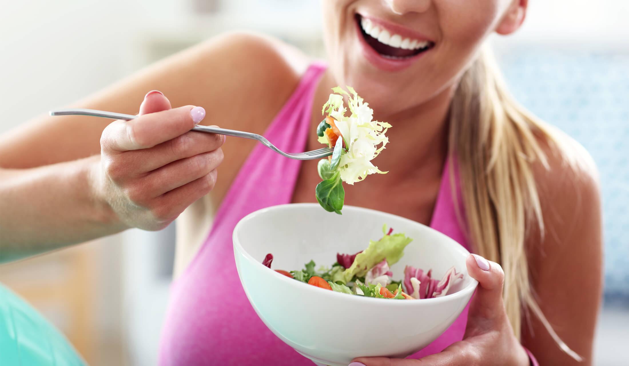 ダイエットをしているピンク色のタンクトップを着た女性がサラダを食べようとしている様子