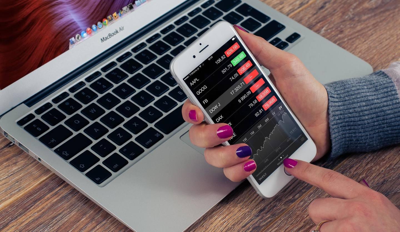 スマートフォンで株価を見る女性の手元