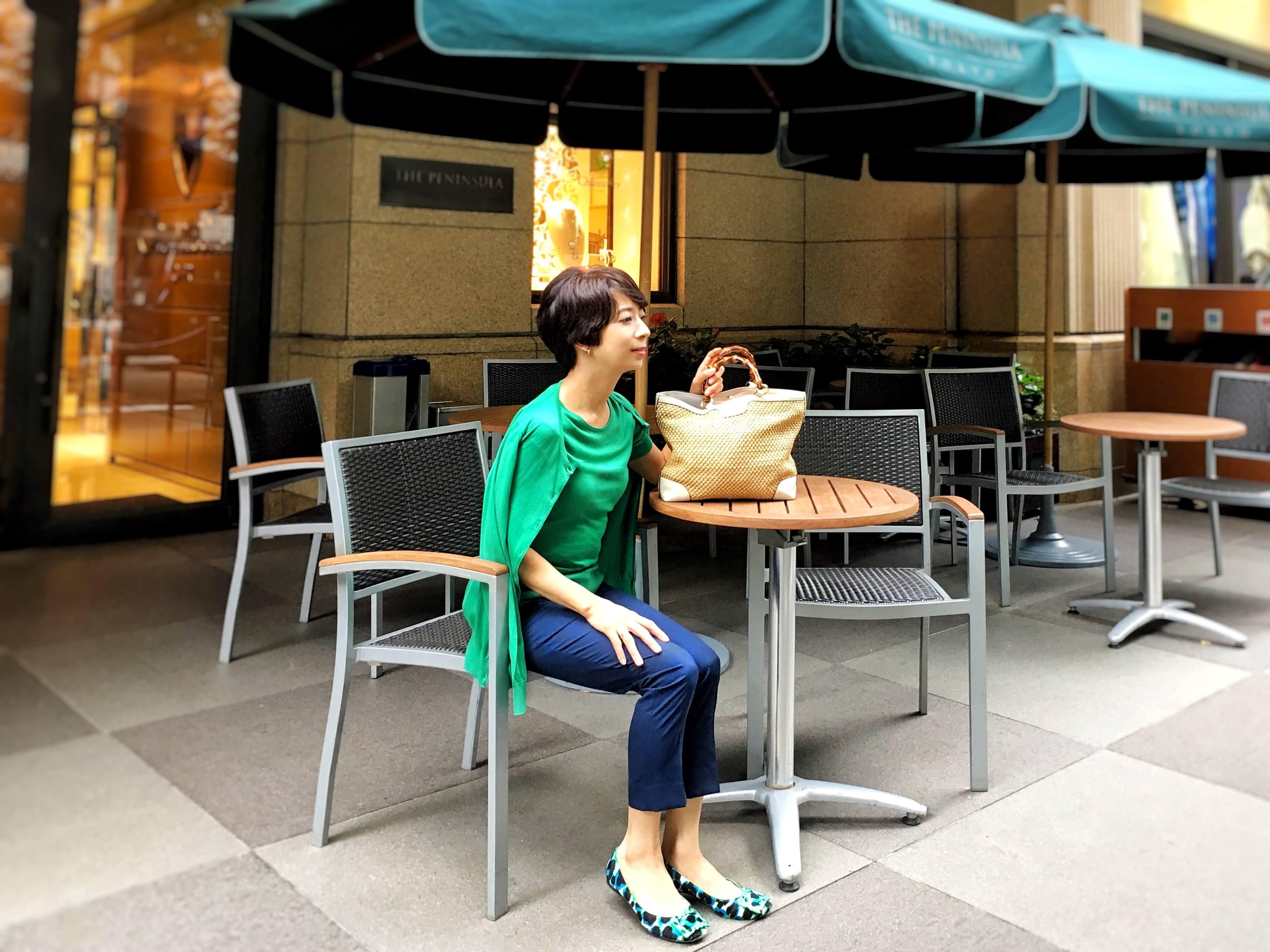 グリーンのツインニットとくるぶし丈のパンツを履いた女性がカフェに座っている図
