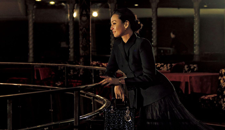 ディオールの黒のジャケット・スカート・バッグ・靴・アクセサリーを身に着けた女性の写真