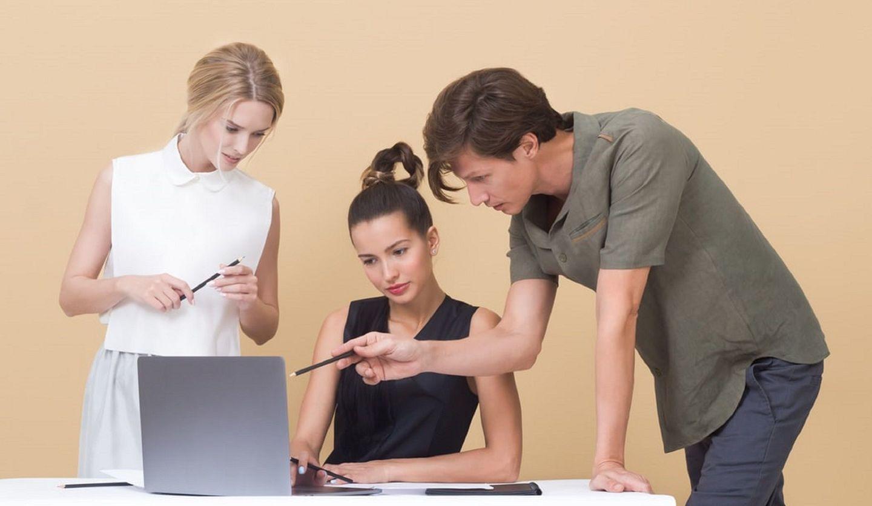 パソコンを見ながら話し合う女性二人と男性一人